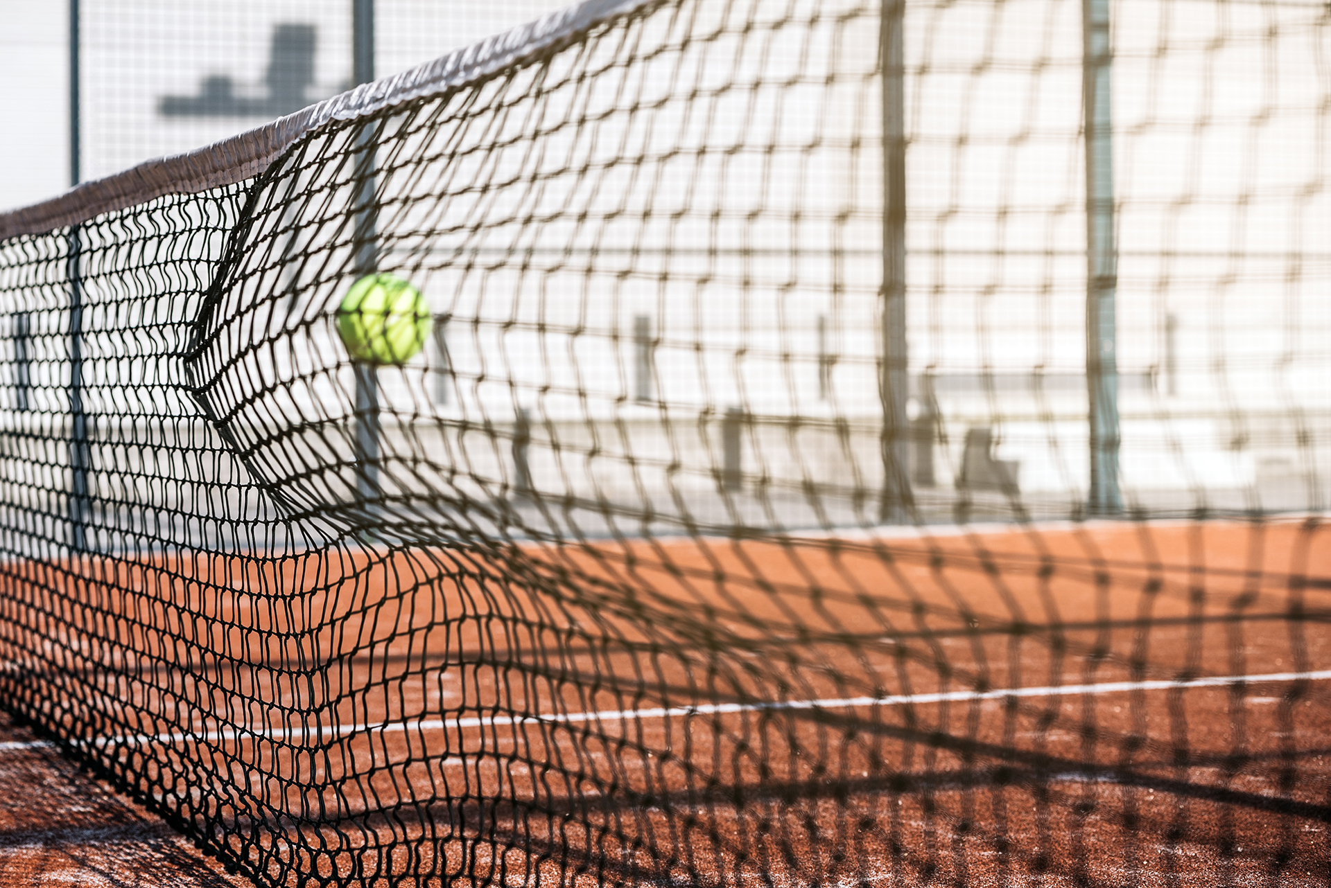 ball in net in a padel court with orange grass